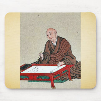 An old man seated a low table, writing mousepads