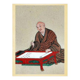 An old man seated a low table, writing postcard