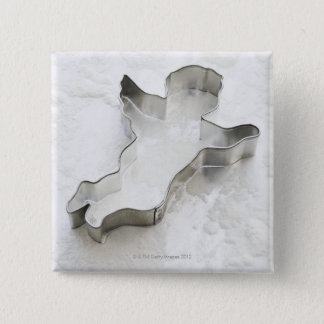 Angel shaped cookie cutter, with flour, close-up 2 inch square button