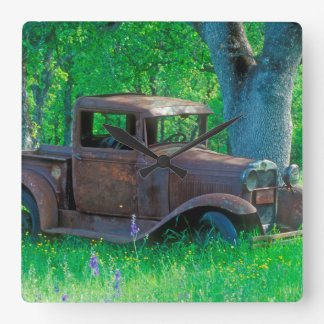 Antique rusted truck in a meadow square wall clock