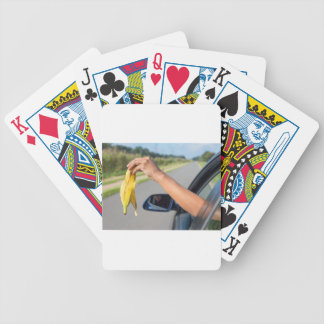 Arm dropping peel of banana out car window bicycle playing cards