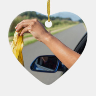 Arm dropping peel of banana out car window ceramic heart ornament