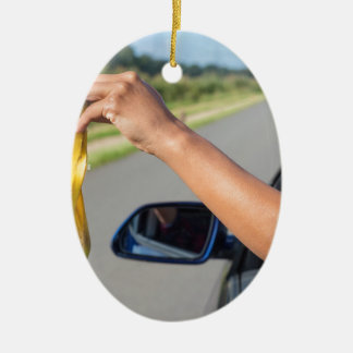 Arm dropping peel of banana out car window ceramic oval ornament