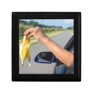Arm dropping peel of banana out car window gift box