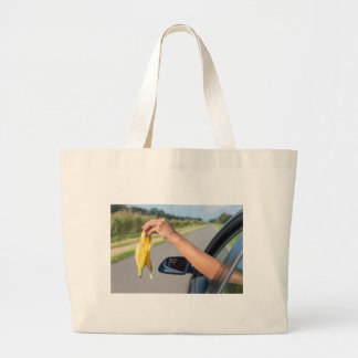 Arm dropping peel of banana out car window large tote bag