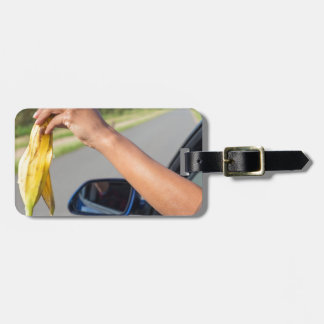 Arm dropping peel of banana out car window luggage tag