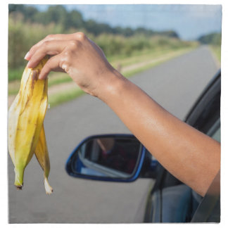 Arm dropping peel of banana out car window napkin