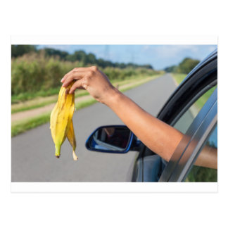 Arm dropping peel of banana out car window postcard