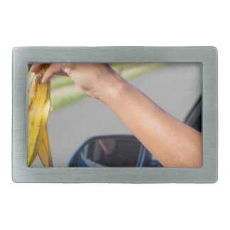 Arm dropping peel of banana out car window rectangular belt buckles