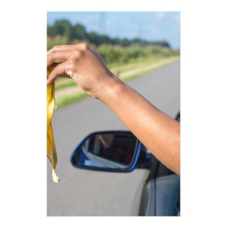 Arm dropping peel of banana out car window stationery