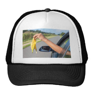 Arm dropping peel of banana out car window trucker hat