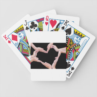Arms and hands of girls making heart shape bicycle playing cards
