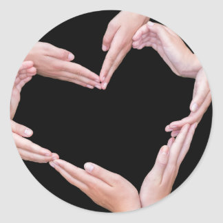 Arms and hands of girls making heart shape classic round sticker