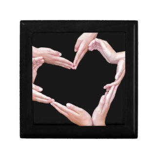 Arms and hands of girls making heart shape gift box