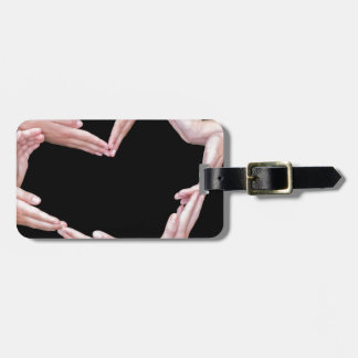 Arms and hands of girls making heart shape luggage tag