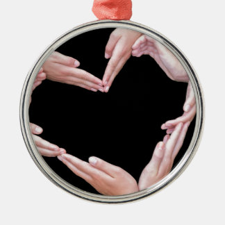 Arms and hands of girls making heart shape metal ornament