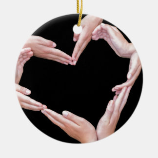 Arms and hands of girls making heart shape round ceramic ornament