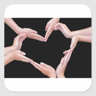 Arms and hands of girls making heart shape square sticker