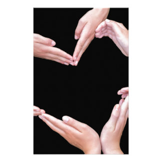 Arms and hands of girls making heart shape stationery