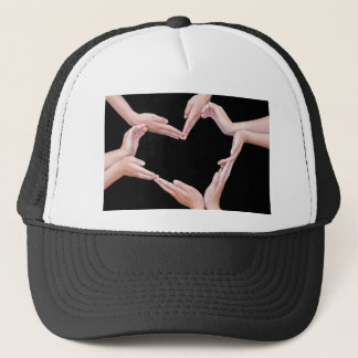 Arms and hands of girls making heart shape trucker hat