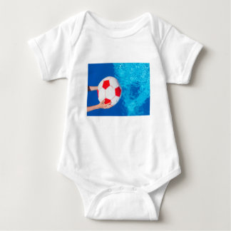 Arms holding beach ball above swimming pool water baby bodysuit