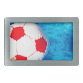 Arms holding beach ball above swimming pool water belt buckle