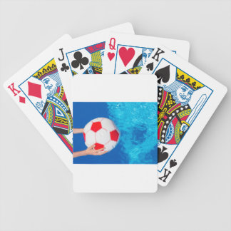 Arms holding beach ball above swimming pool water bicycle playing cards