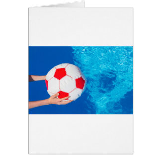 Arms holding beach ball above swimming pool water card
