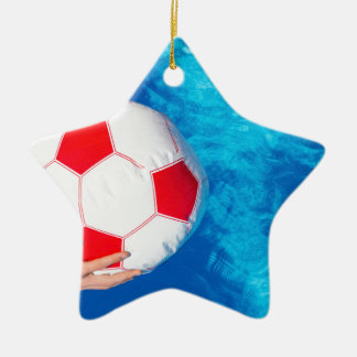 Arms holding beach ball above swimming pool water ceramic star ornament