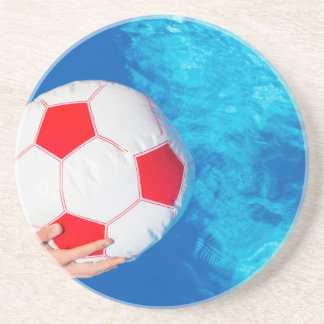 Arms holding beach ball above swimming pool water coaster