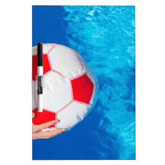 Arms holding beach ball above swimming pool water dry erase white board