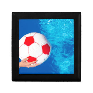 Arms holding beach ball above swimming pool water gift box