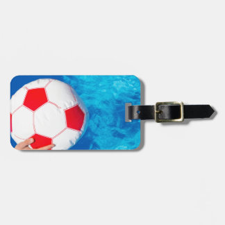 Arms holding beach ball above swimming pool water luggage tag