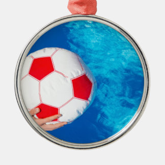 Arms holding beach ball above swimming pool water metal ornament