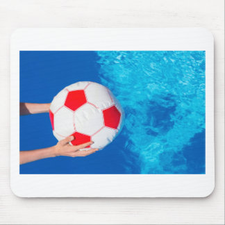 Arms holding beach ball above swimming pool water mouse pad