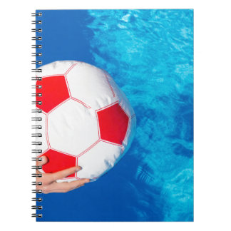 Arms holding beach ball above swimming pool water notebooks