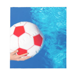 Arms holding beach ball above swimming pool water notepads