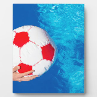 Arms holding beach ball above swimming pool water plaque
