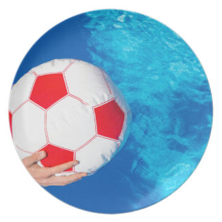 Arms holding beach ball above swimming pool water plate