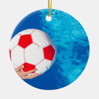Arms holding beach ball above swimming pool water round ceramic ornament