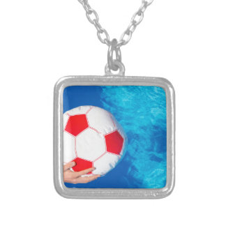 Arms holding beach ball above swimming pool water silver plated necklace