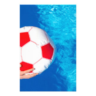 Arms holding beach ball above swimming pool water stationery