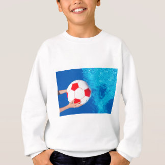 Arms holding beach ball above swimming pool water sweatshirt