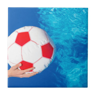 Arms holding beach ball above swimming pool water tiles