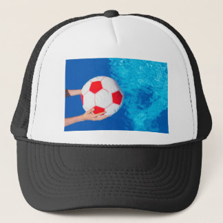 Arms holding beach ball above swimming pool water trucker hat
