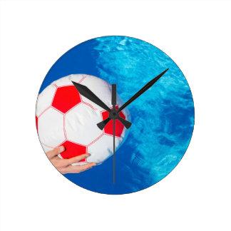 Arms holding beach ball above swimming pool water wallclocks