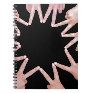 Arms of girls  hands making ten pointed star notebook