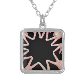 Arms of girls  hands making ten pointed star silver plated necklace