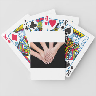 Arms of girls with hands over each other bicycle playing cards