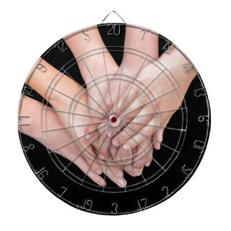 Arms of girls with hands over each other dartboard